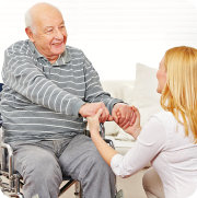 old man and caregiver holding hands